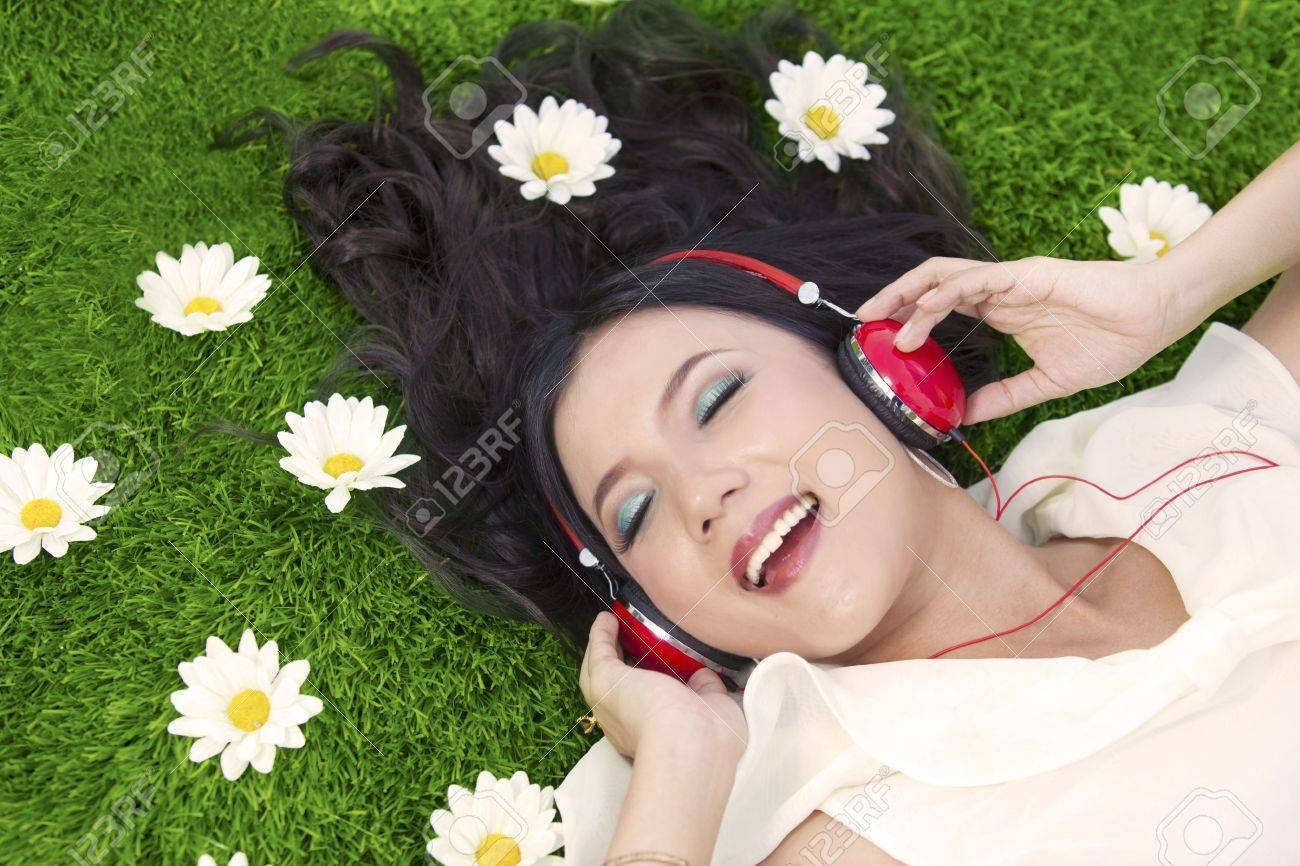 Beautiful woman listens to music while laying on the grass with flowers Stock Photo - 14779094