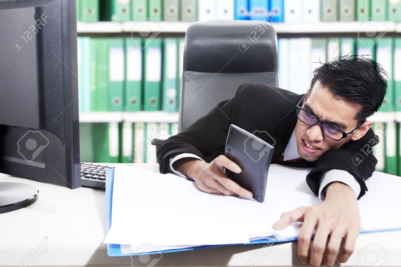 young accountant calculate his finance by using calculator at stock photo young accountant calculate his finance by using calculator at office