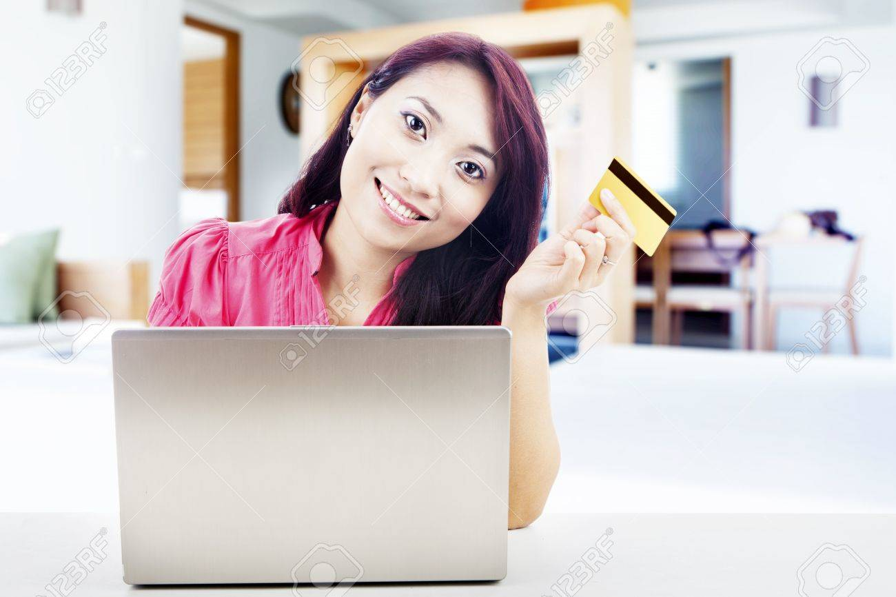 Smiling young asian woman holding a credit card with laptop computer. shot at home Stock Photo - 15474320