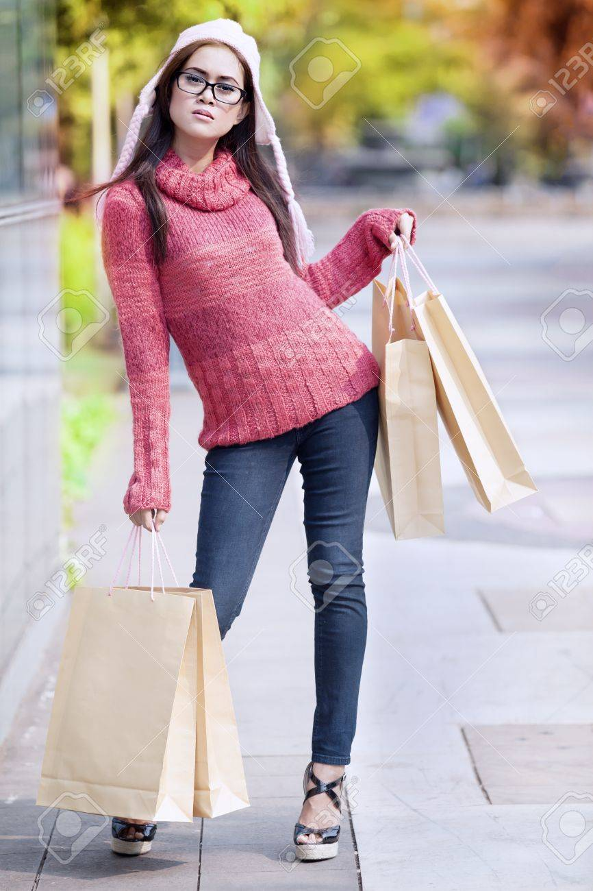 Portrait of glamour girl carrying shopping bag and dressed for winter time with hat on her head. Stock Photo - 15474189