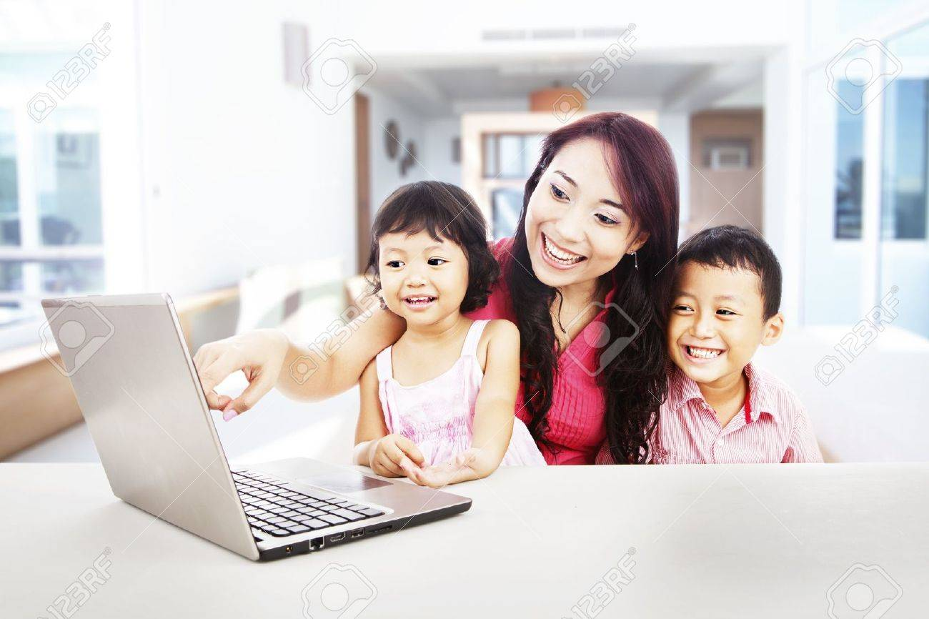 Happy young mother with her children using ultrabook laptop computer to enjoy entertainment at home Stock Photo - 15474361