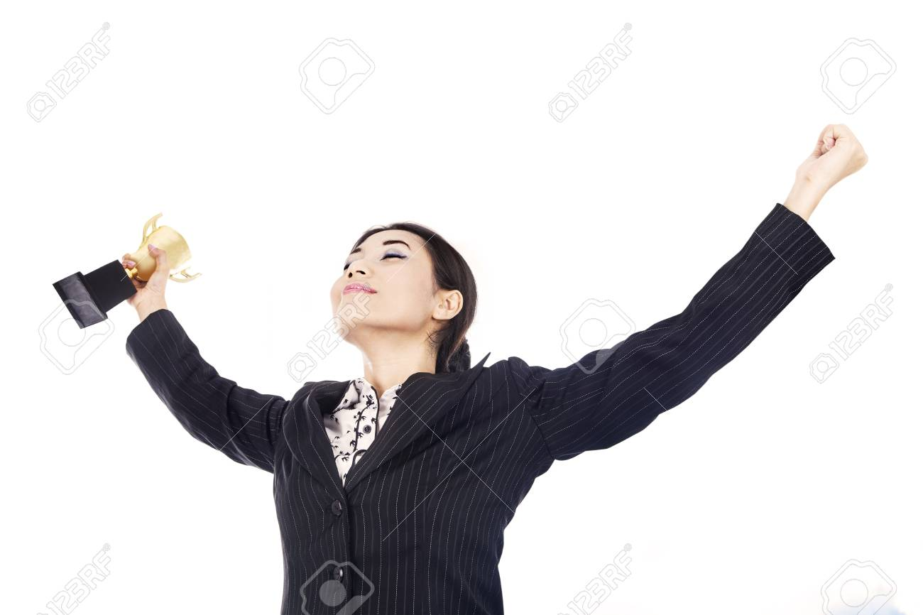 A happy businesswoman celebrating her winning holding the trophy isolated over white Stock Photo - 15637880