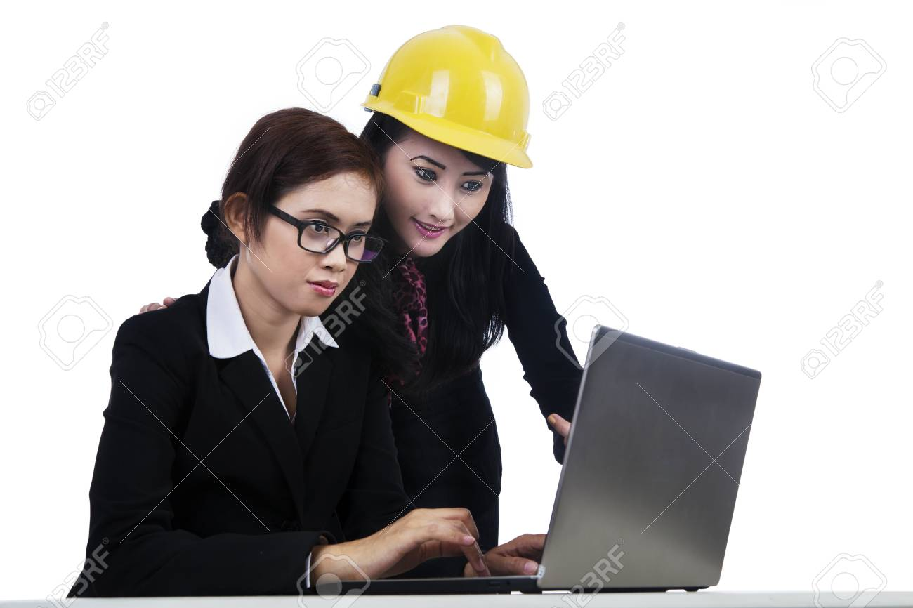 Two young architects working together on a laptop isolated in white Stock Photo - 16011270