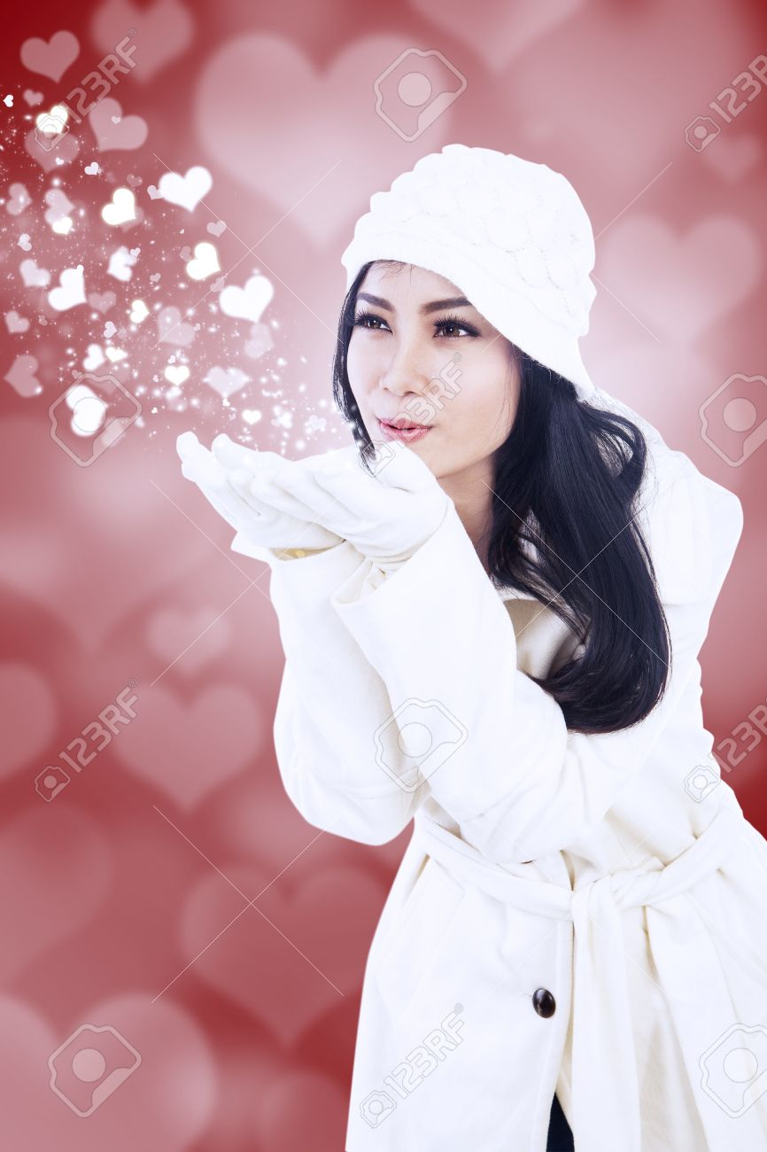 Beautiful girl blowing valentine kiss on red background Stock Photo - 16660525