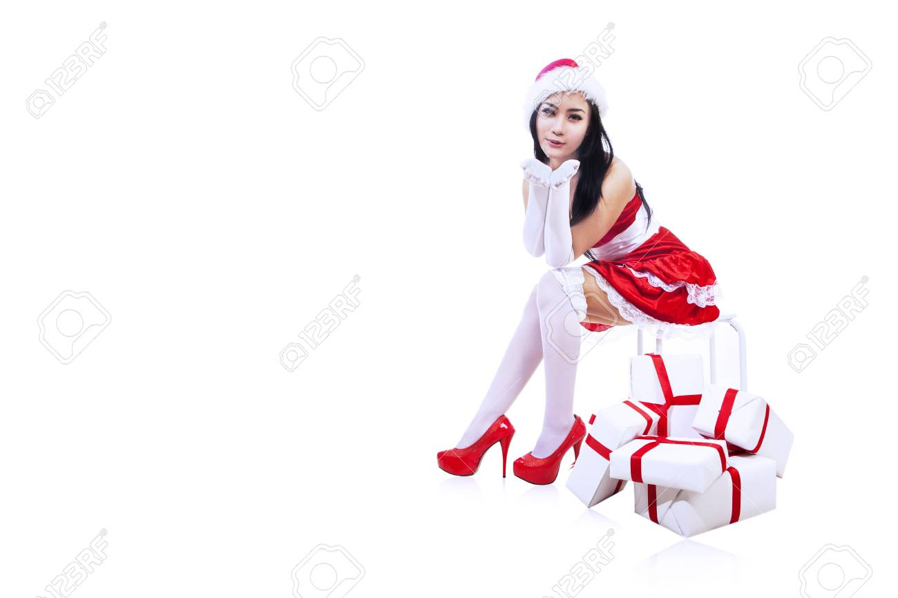 Attractive Mrs Claus is looking at camera while sitting, isolated in white Stock Photo - 16660517