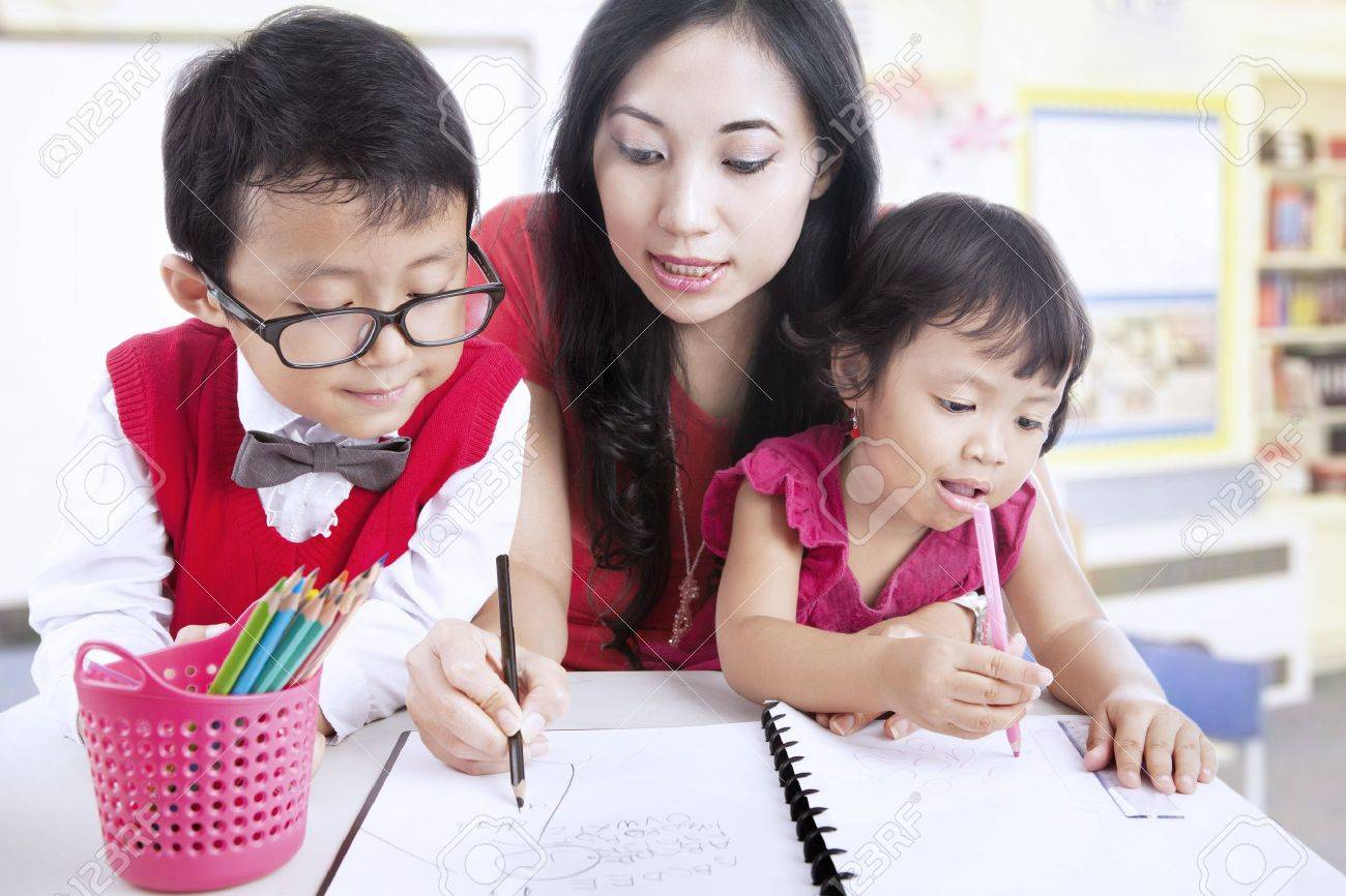 Beautiful mother teaches her children to write in class Stock Photo - 16823447