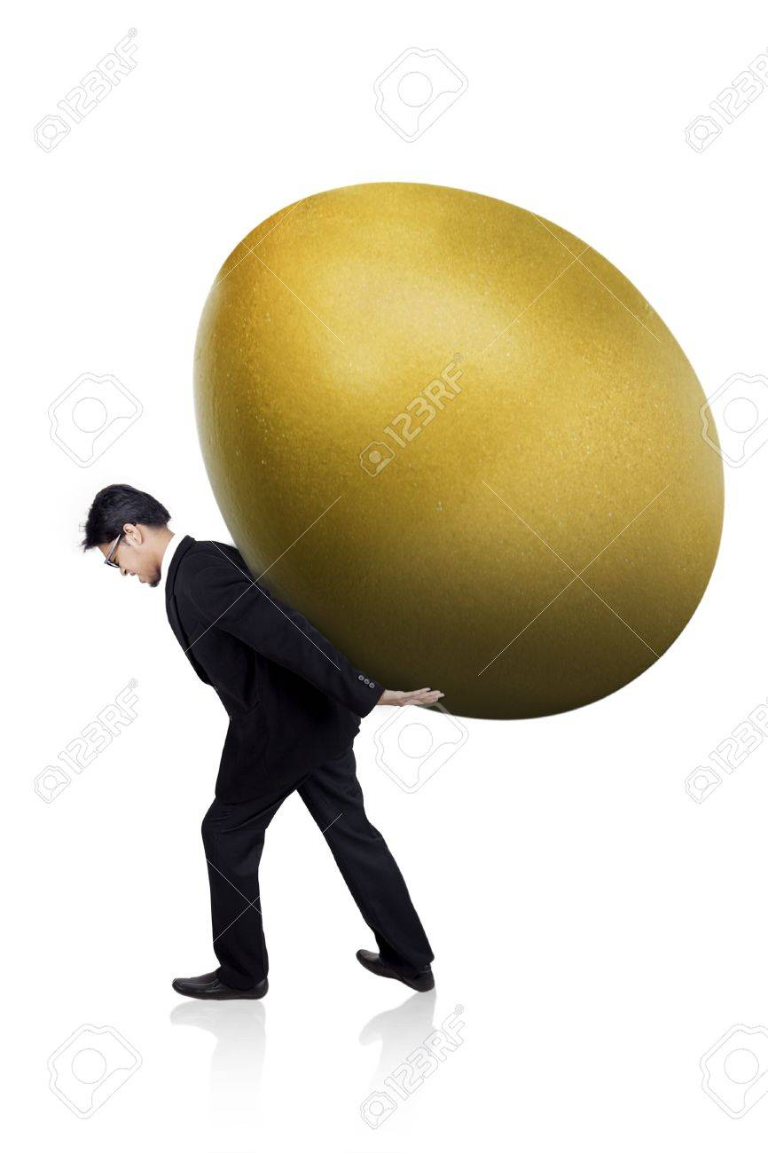 Businessman is carrying a huge golden egg isolated on white Stock Photo - 17824179