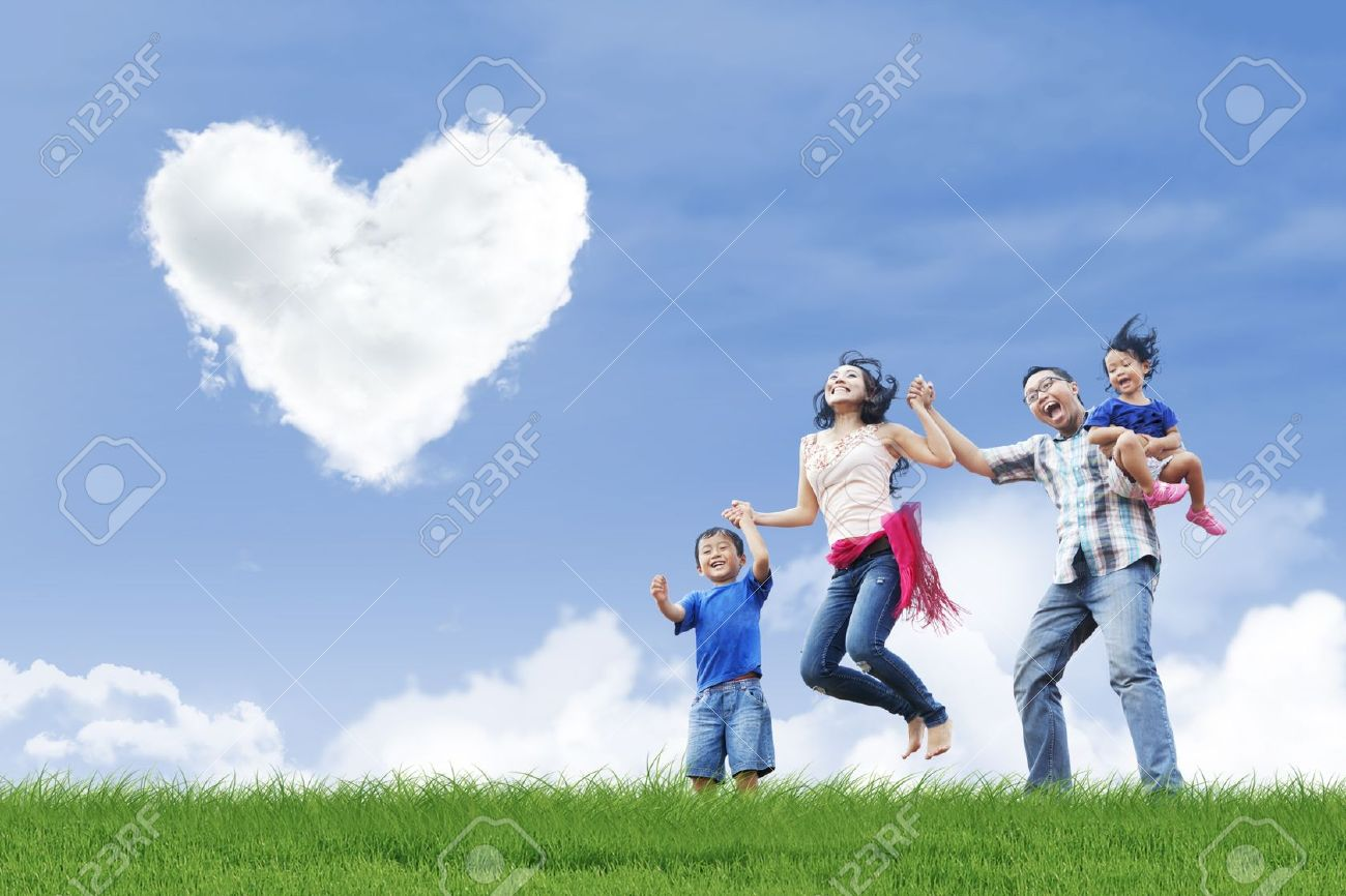 Happy family is having fun under love shape clouds in the park Stock Photo - 17824182