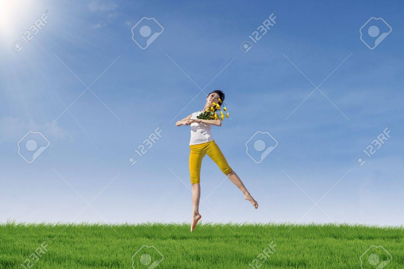 Beautiful woman dancing in the park while holding yellow flowers Stock Photo - 18020572