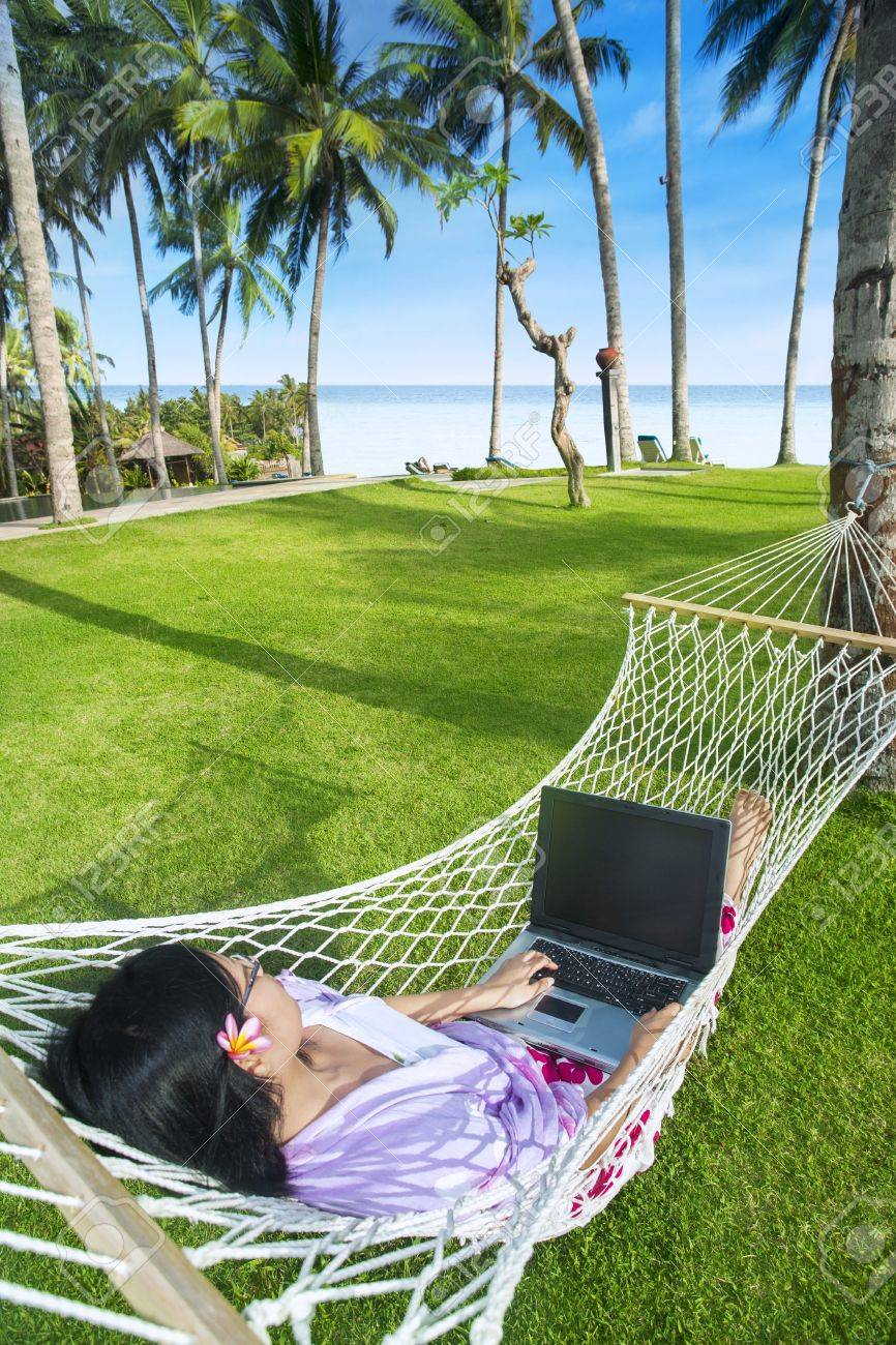 Asian girl work in hammock with laptop at Bali beach, Indonesia Stock Photo - 19564085