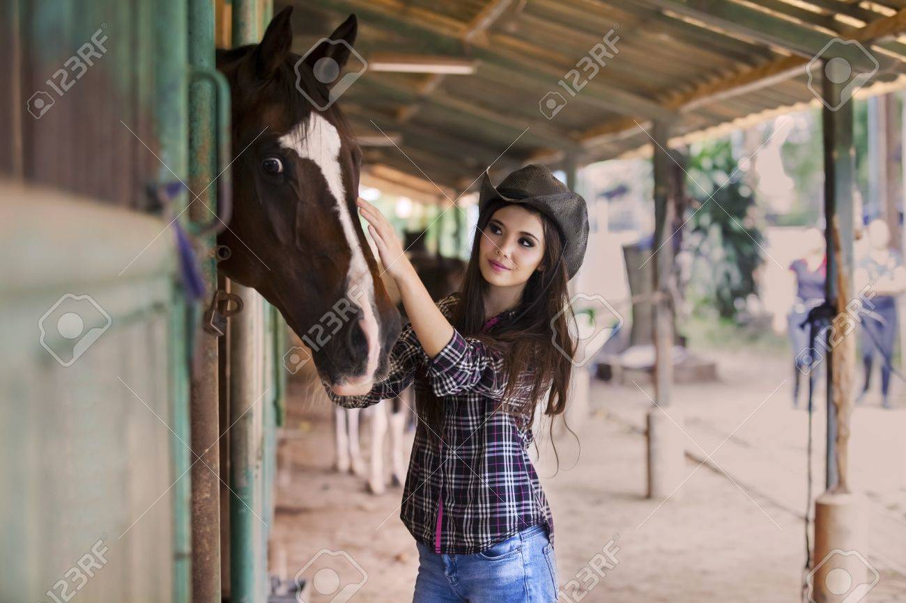 Beautiful cowboy girl stroking her horse at ranch Stock Photo - 19564071