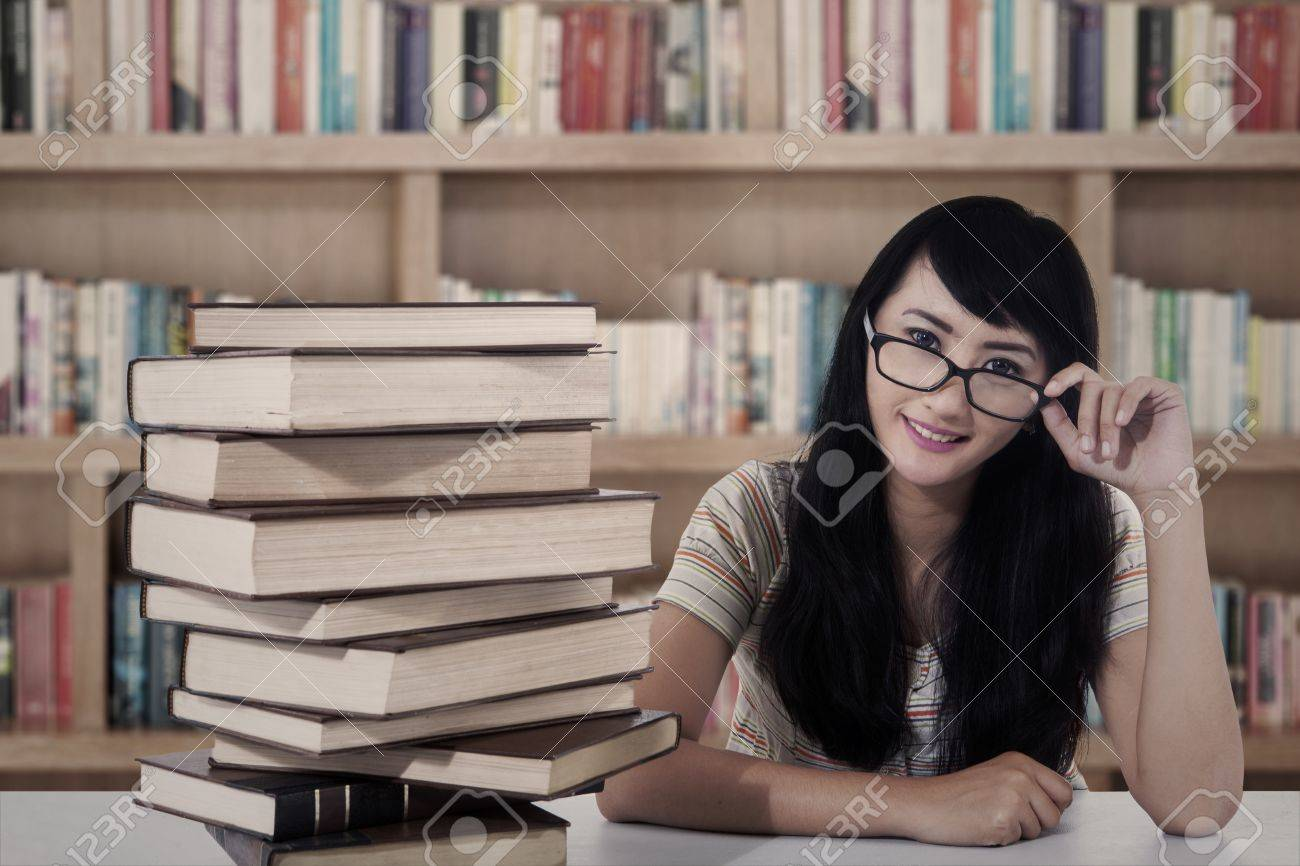 Beautiful female student sitting in the library with books Stock Photo - 20709528