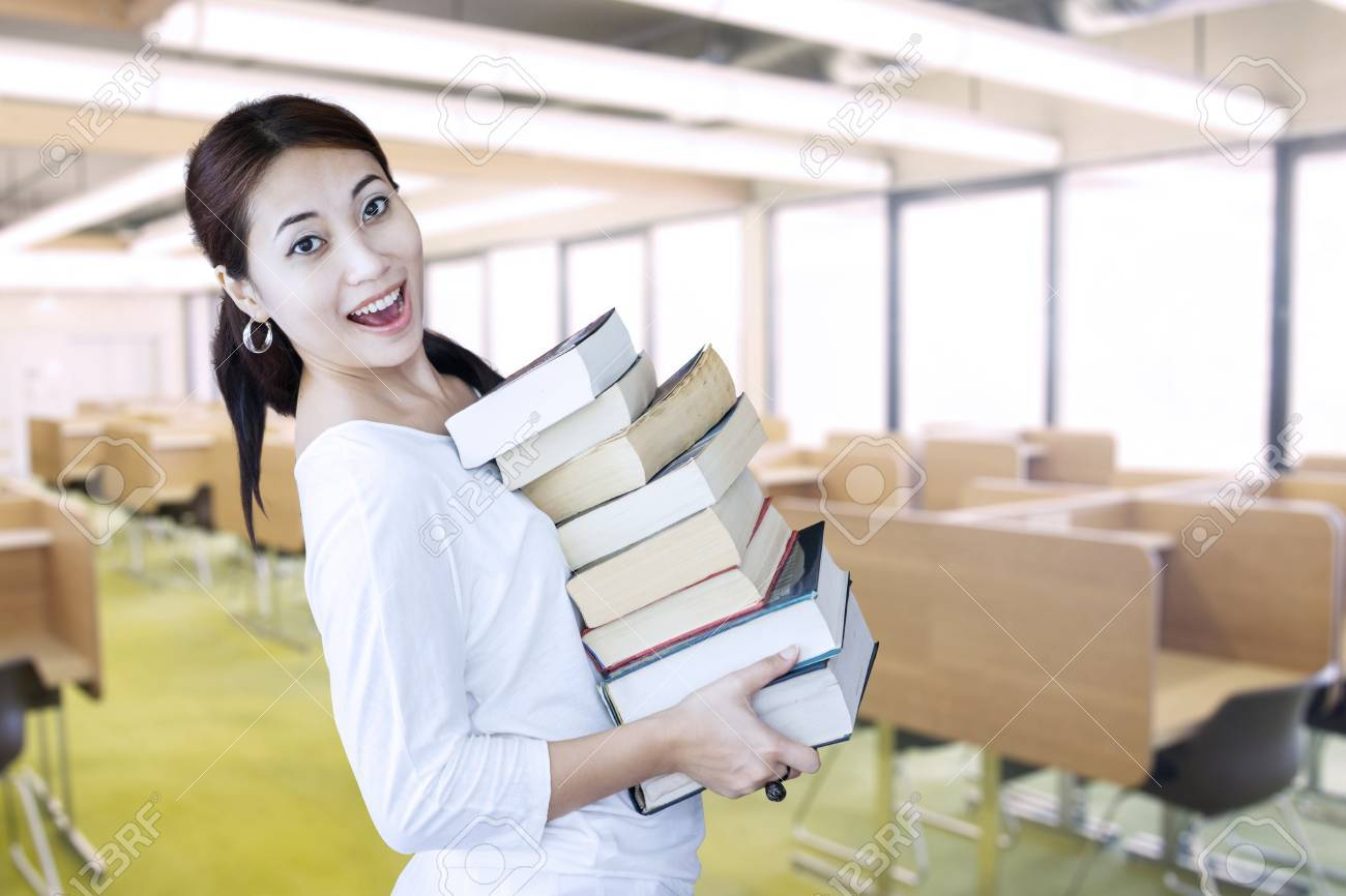 Attractive Asian female student bring pile of books in library Stock Photo - 20733471