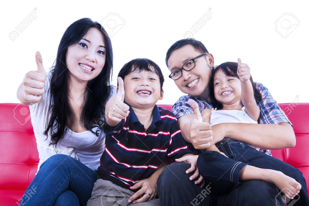 Isolated picture of family members showing thumbs up on red sofa Stock Photo - 20922896