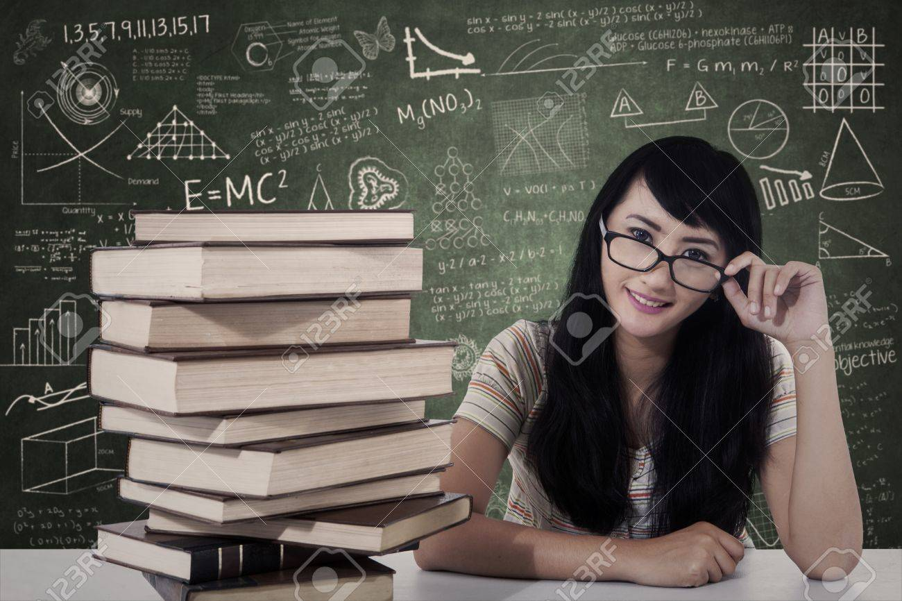 Beautiful female student study in class with stack of books Stock Photo - 20990536