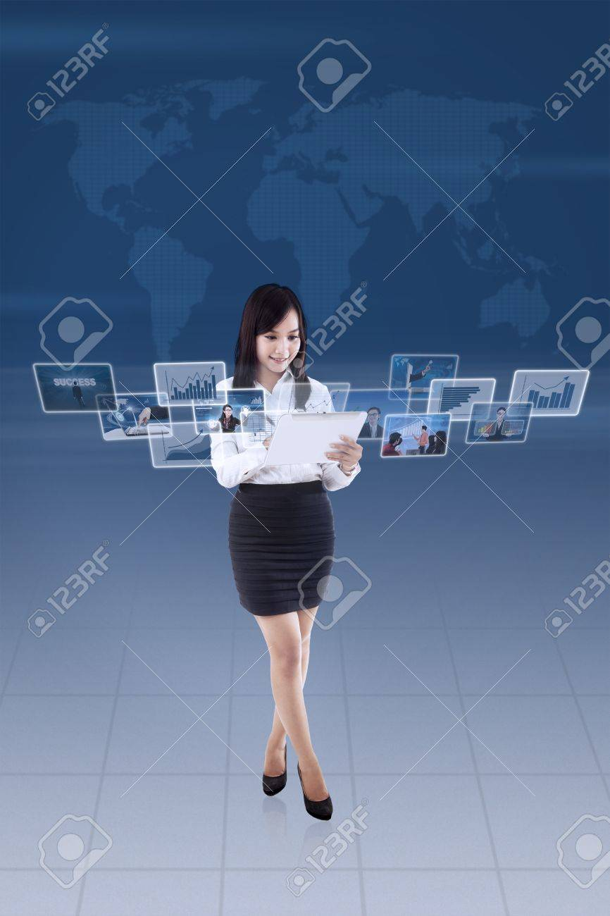 Businesswoman is looking at online pictures on e-tablet with blue world map background Stock Photo - 21053239