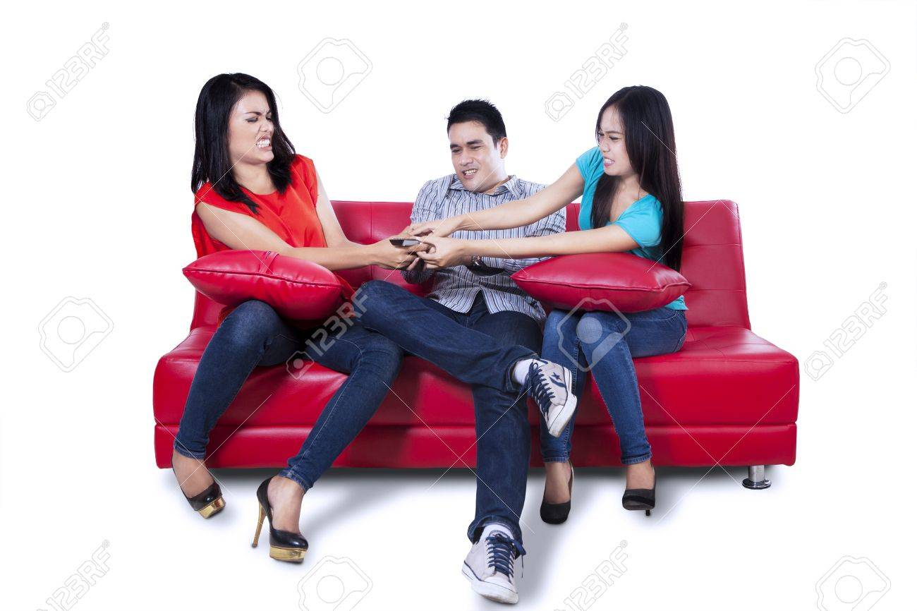 Three young teenagers watching television and fighting for remote control Stock Photo - 22126320