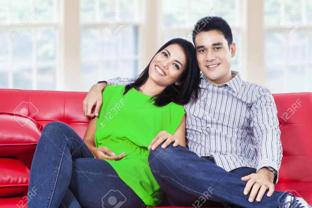 Happy young couple laughing and looking at camera in a living room Stock Photo - 22173086