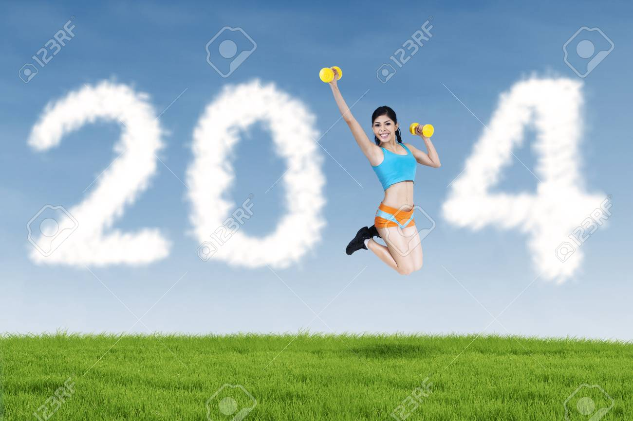 Happy fitness young woman jumping with new year 2014 of clouds Stock Photo - 22491178