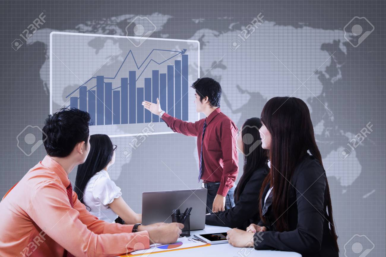 Business team is looking at bar chart on blue world map background Stock Photo - 22653038