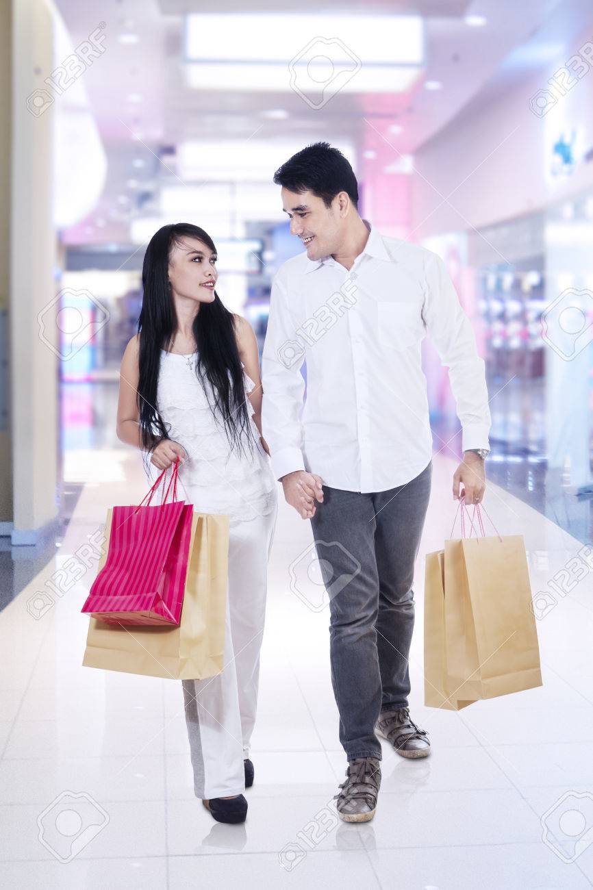 Happy couple walking on the mall carrying shopping bags Stock Photo - 23963335