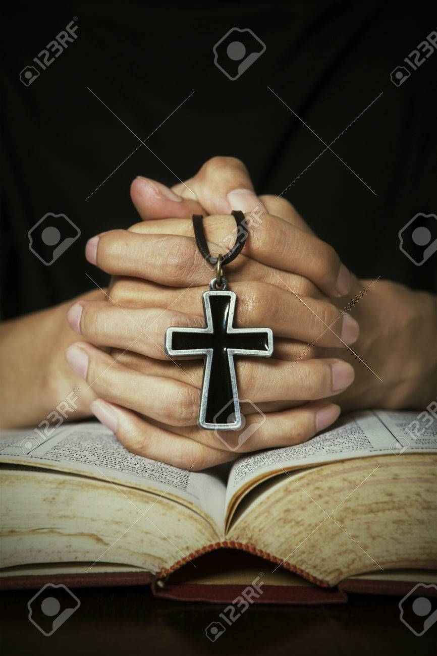 8c2a1018e Closeup of hand praying pose on bible while holding a cross Stock Photo -  26657644