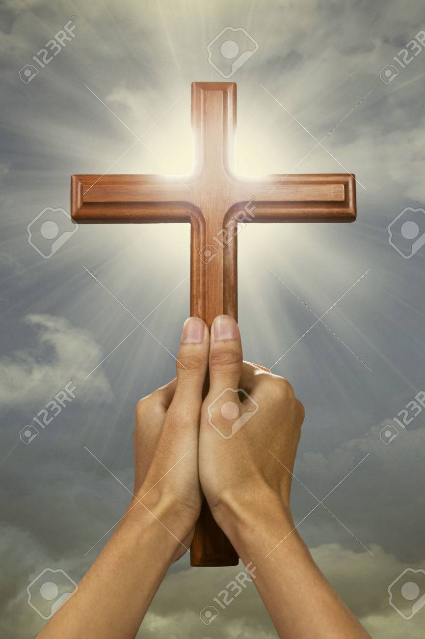 7e63fe467 Closeup of prayer hands holding a cross wood and raising the cross to the  sky Stock