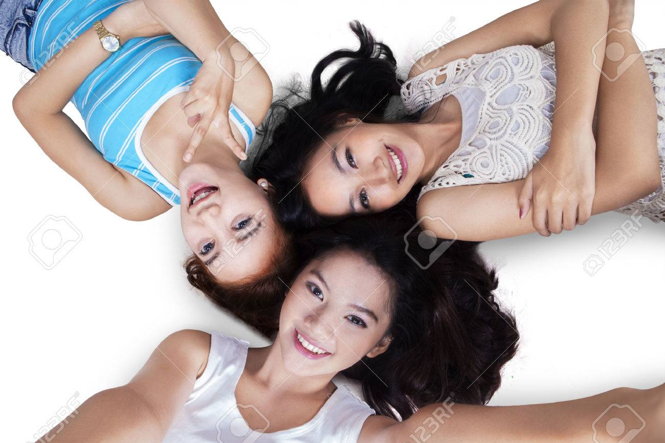 High Angle View Of Excited Teenage Girls Lying Down On The Floor