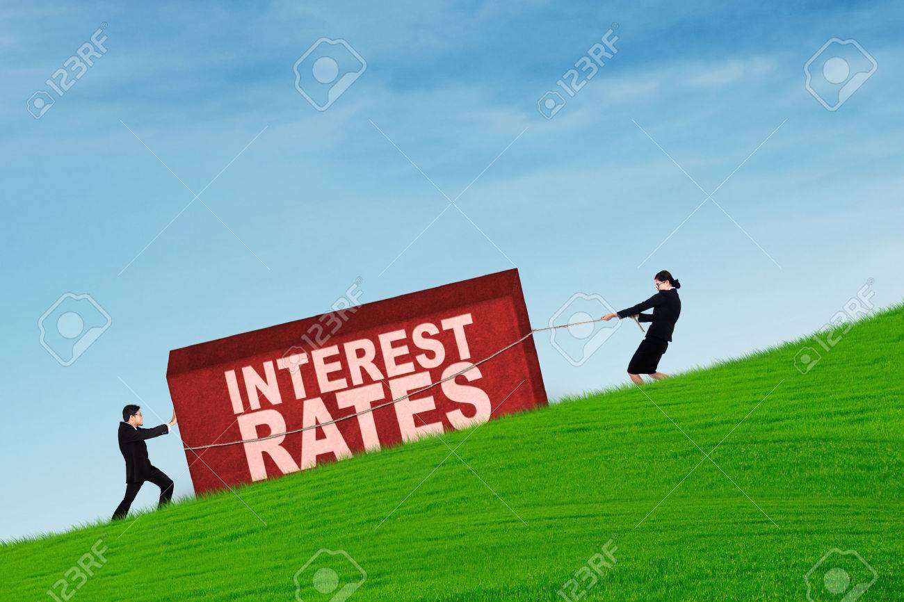 Business people pulling a box with interest rates word on up hill Stock Photo - 45690870