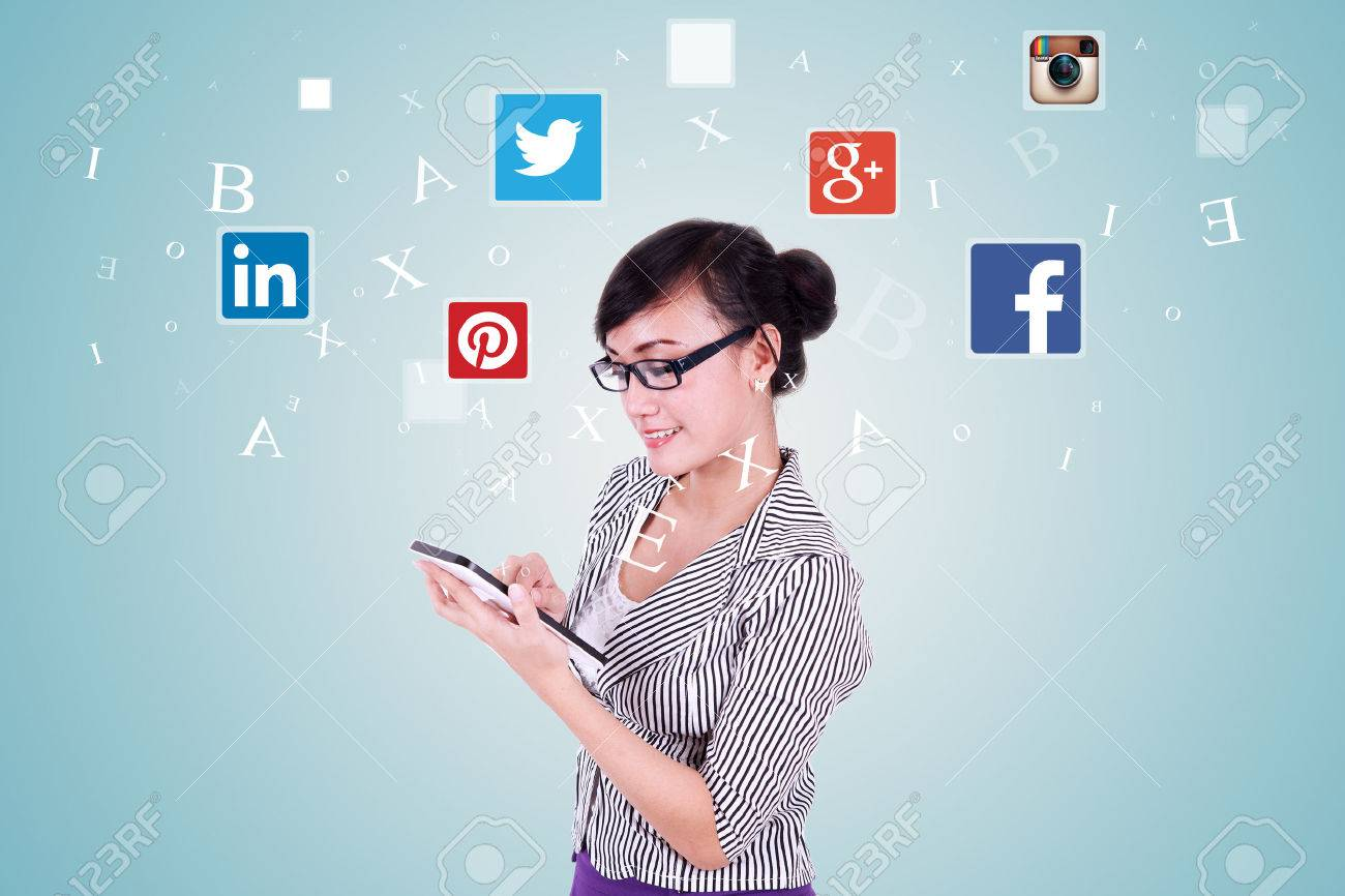 JAKARTA, SEPTEMBER 08, 2015: Image of young asian woman holding and using digital tablet with social media icons: facebook, google plus, instagram, twitter, pinterest, and linkedin Stock Photo - 45146642