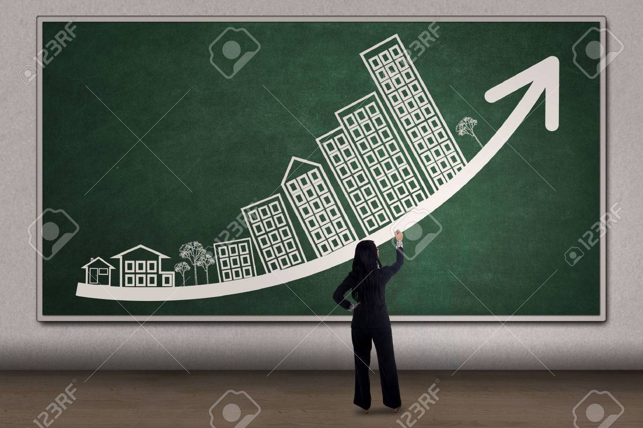 Young businesswoman drawing business property chart with arrow and house picture on the blackboard Stock Photo - 45481857