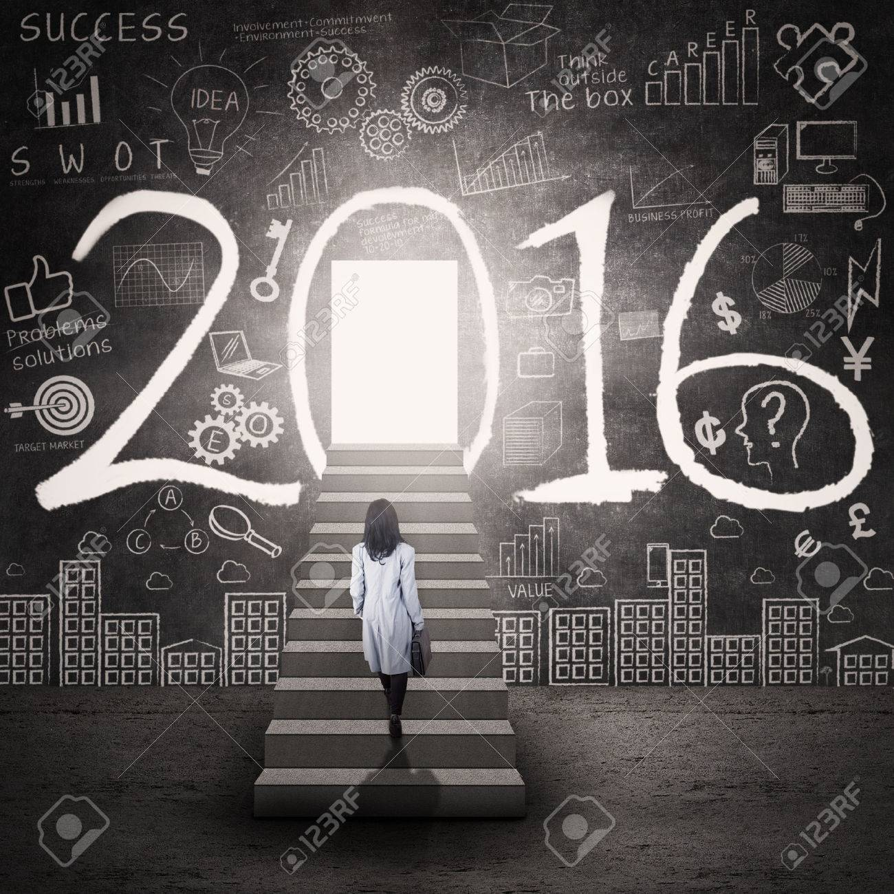 Photo of businesswoman walking on the stairs toward a door with numbers 2016 and scribble Stock Photo - 46391269