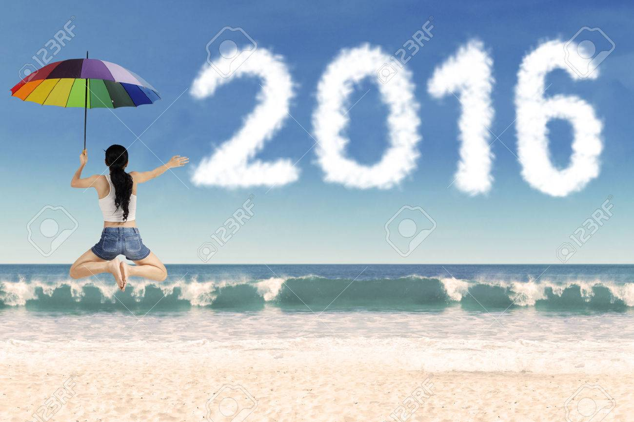 Image of happy woman jumping on the beach while holding umbrella with cloud shaped numbers 2016 Stock Photo - 46391275