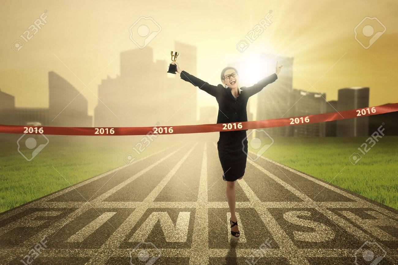 若いビジネス女性レースの競争に勝つとトロフィーを運んでいる間決勝線 ...