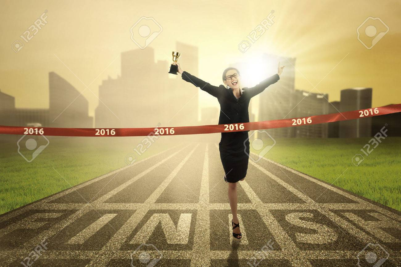 Photo of young business woman winning the race competition and crossing the finish line while carrying a trophy Stock Photo - 46391075
