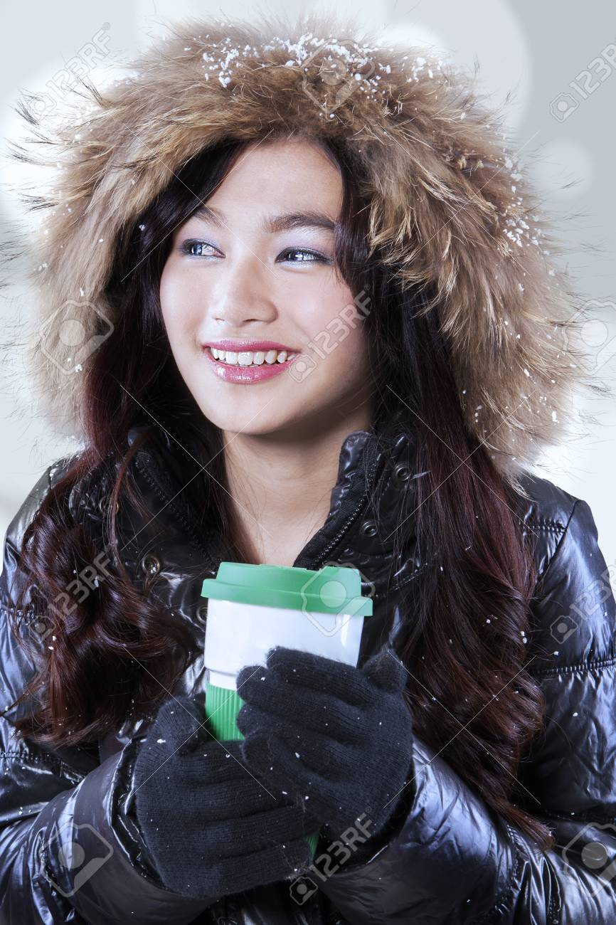 ec6ba8eb7 Gorgeous teenage girl in winter clothing and holding a hot drink with  disposable cup Stock Photo