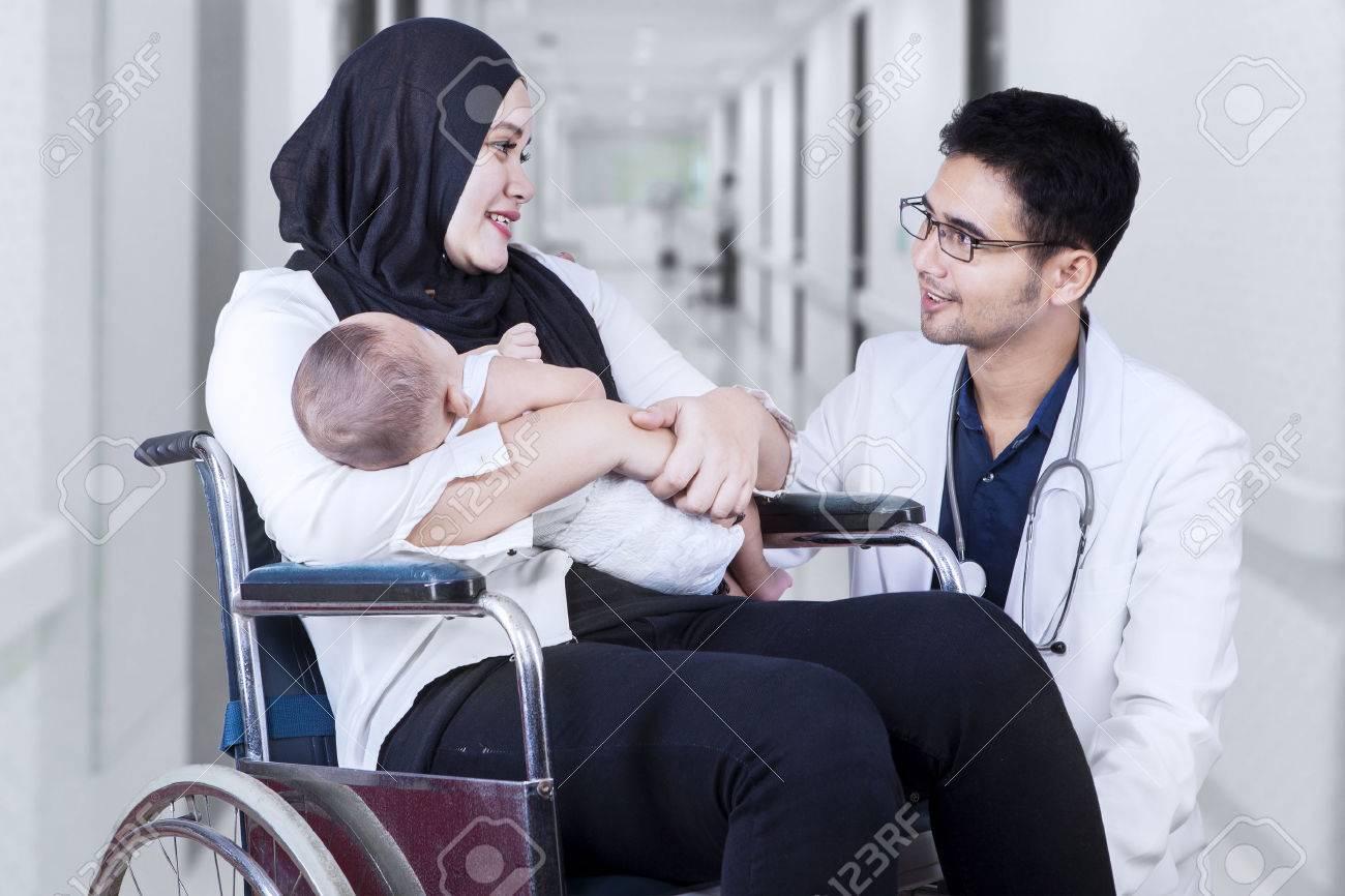 Portrait de médecin de sexe masculin parler avec jeune mère assise sur le fauteuil roulant, tir à l'hôpital Banque d'images - 46729751