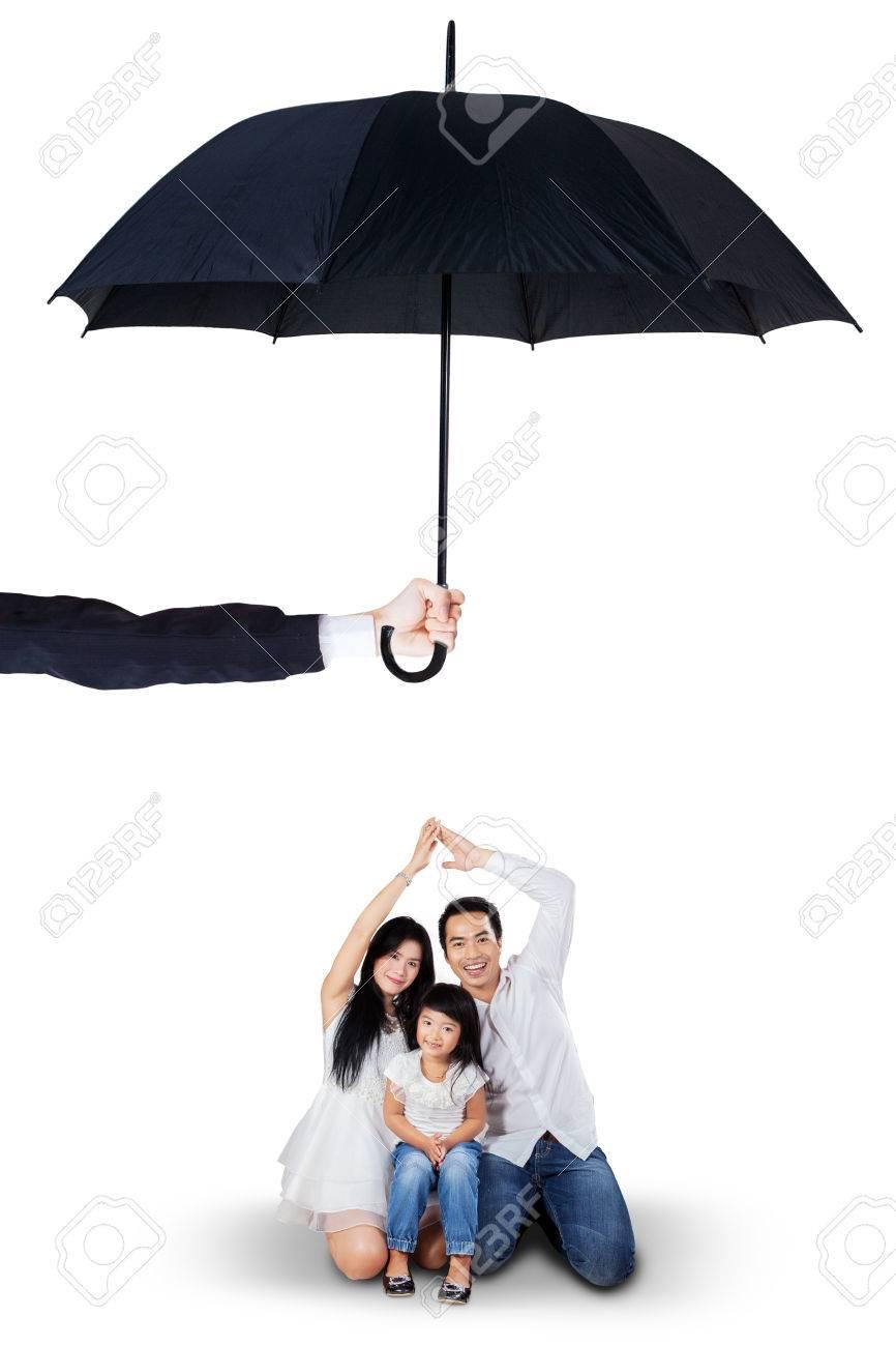 Portrait des parents et leur fille de joie assis dans le studio sous le parapluie. Assurance vie et de la famille notion Banque d'images - 47290090