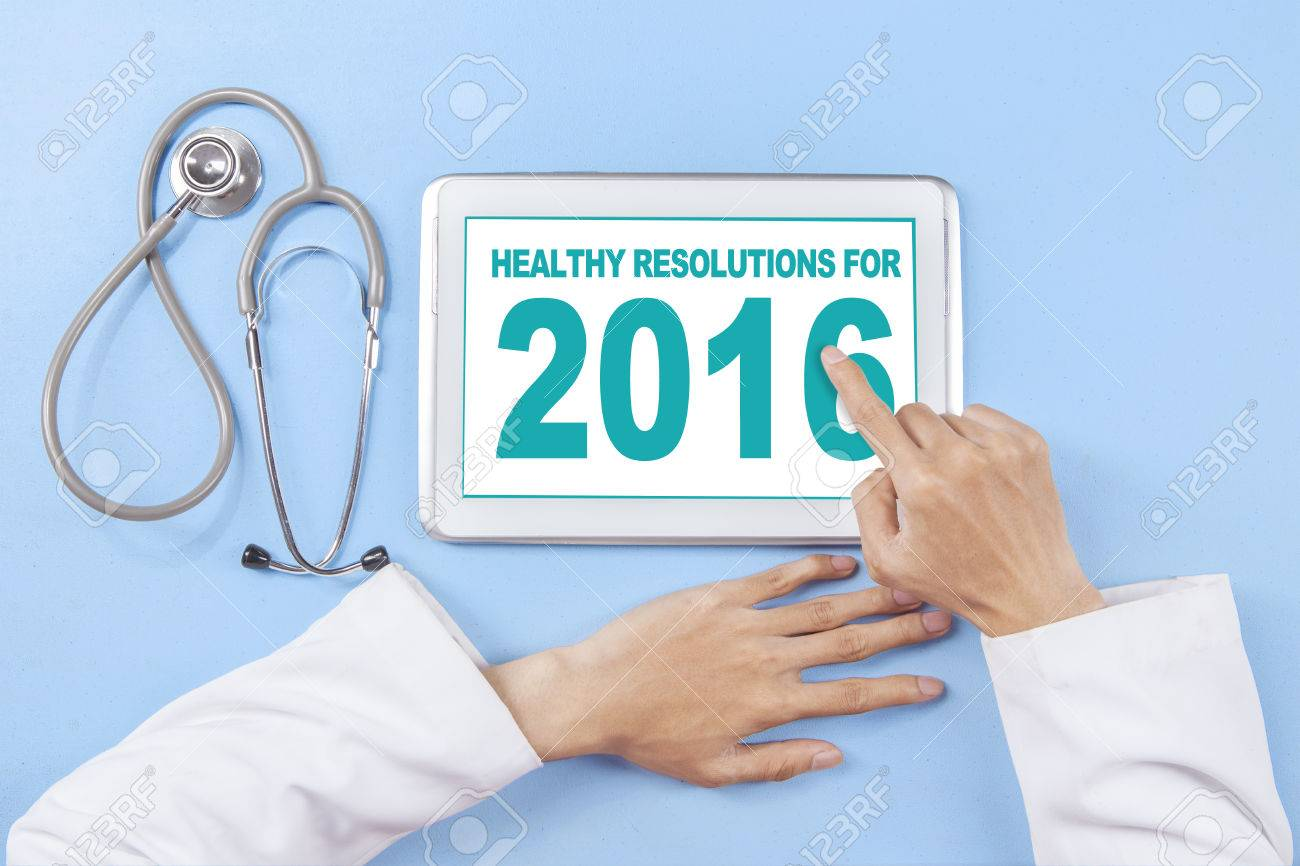 Image of doctor hand using tablet to write healthy resolution for 2016 on the screen Stock Photo - 48554070