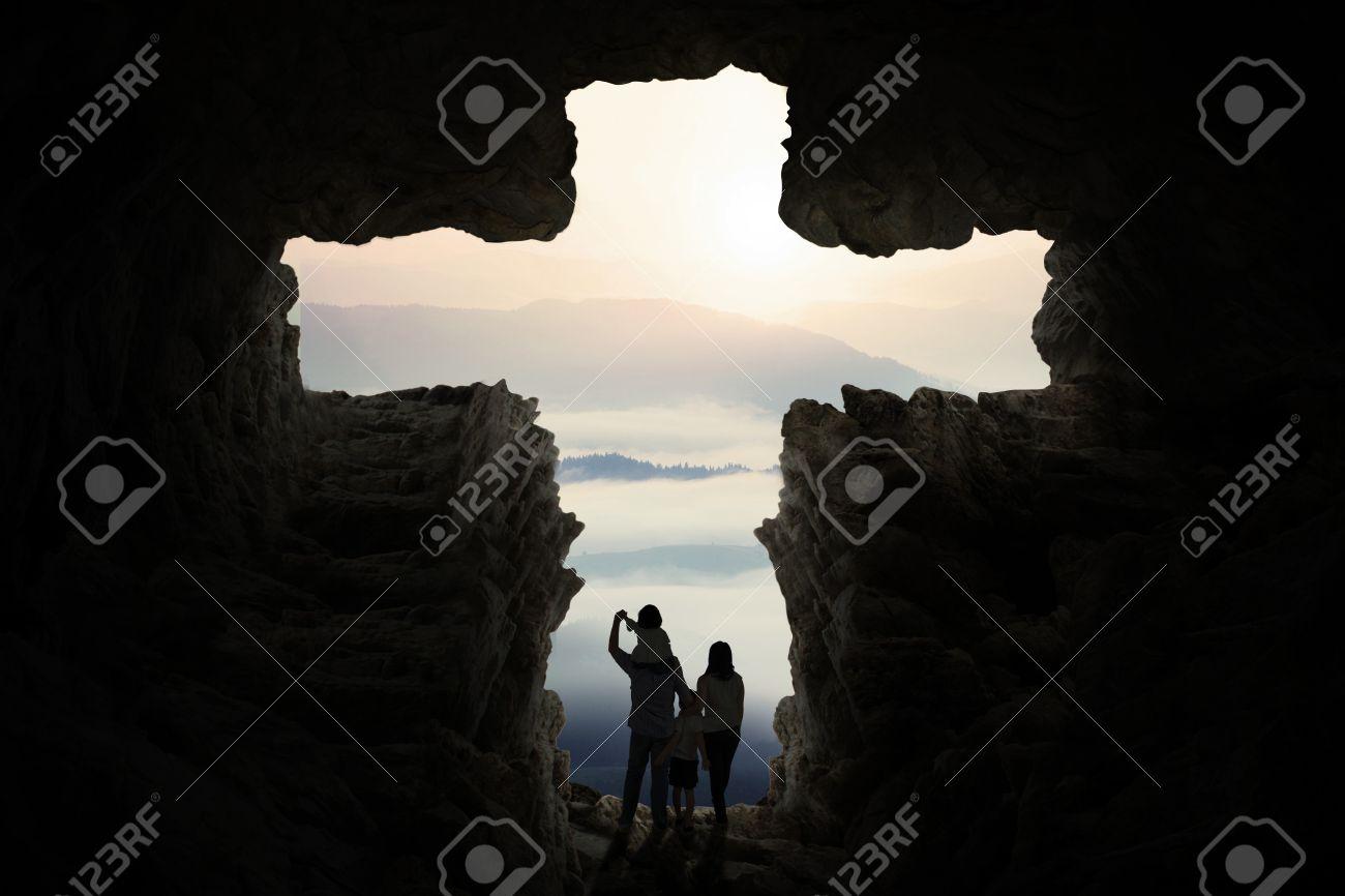Silhouette de deux parents et de leurs enfants à l'intérieur de la grotte debout forme une croix Banque d'images - 48741960