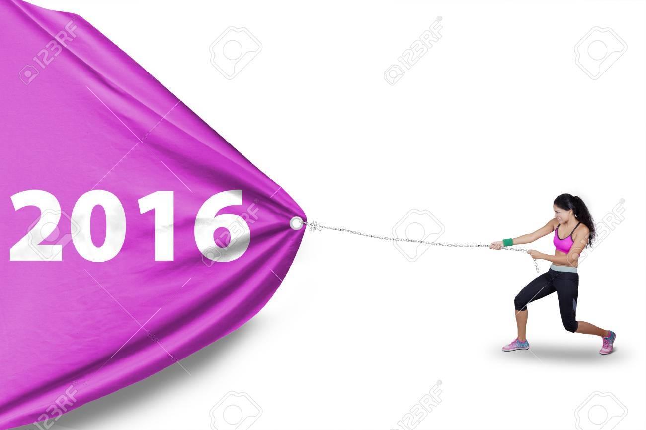Photo de femme indienne saine porter des vêtements de sport et en tirant un grand drapeau avec les chiffres de 2016 en studio Banque d'images - 49008682