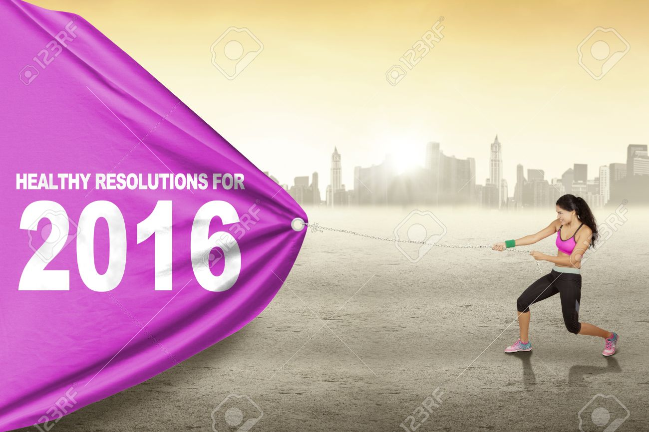 Pretty indian woman wearing sportswear and pulls text of healthy resolution for 2016 with a big flag Stock Photo - 49009646