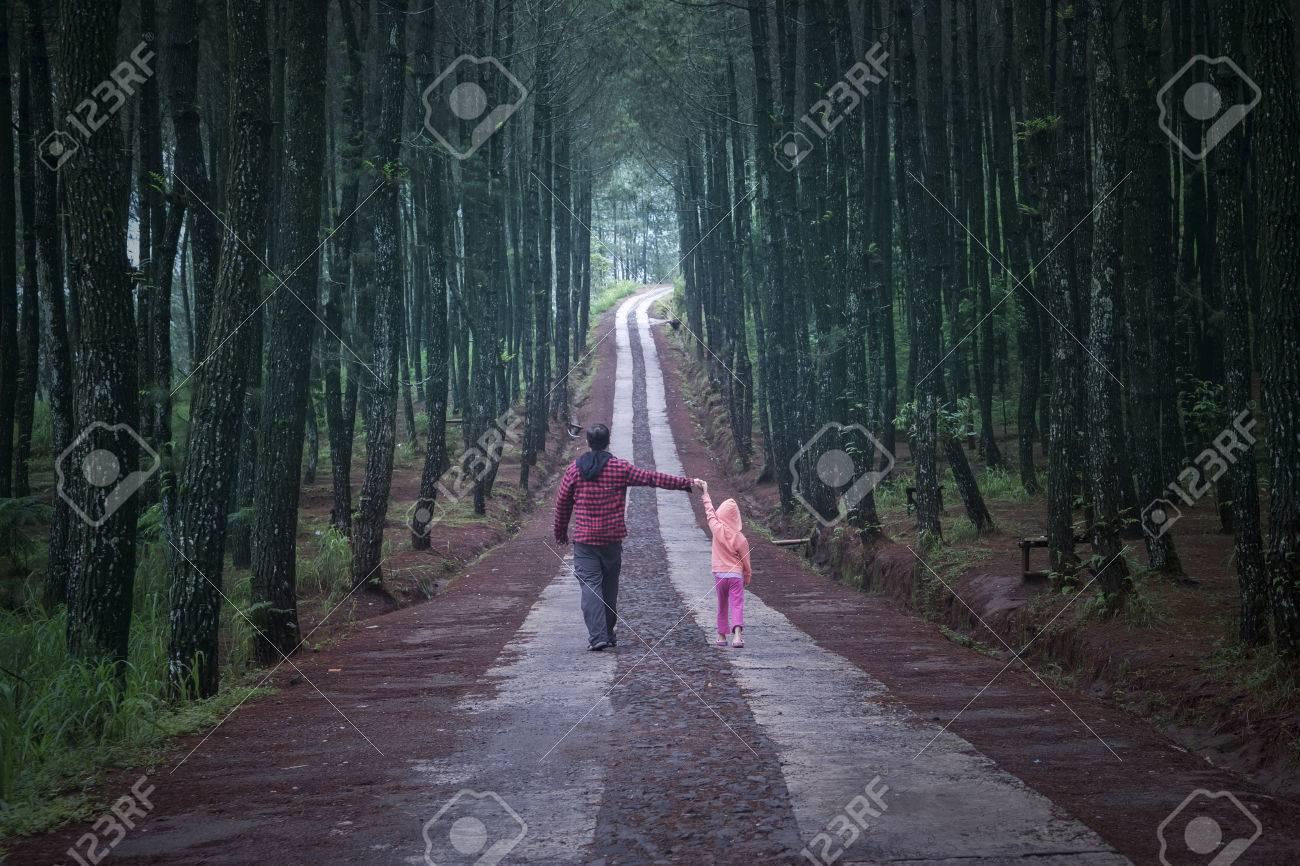 Jeune homme marchant dans la forêt de pins tout en tenant la main avec sa fille Banque d'images - 51239030