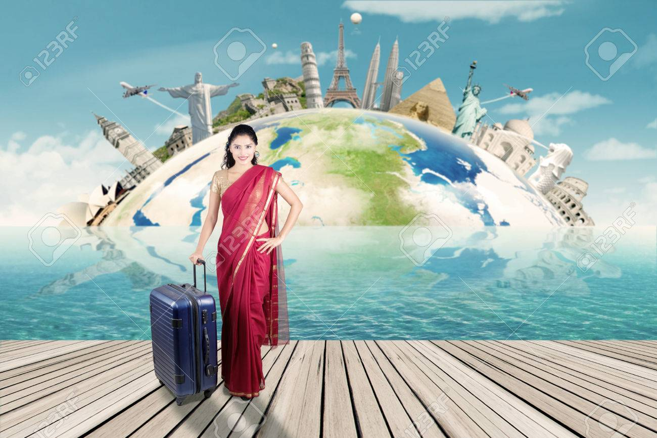Beautiful indian woman carrying suitcase with map of world monument. Concept of travel around the world - 51606568
