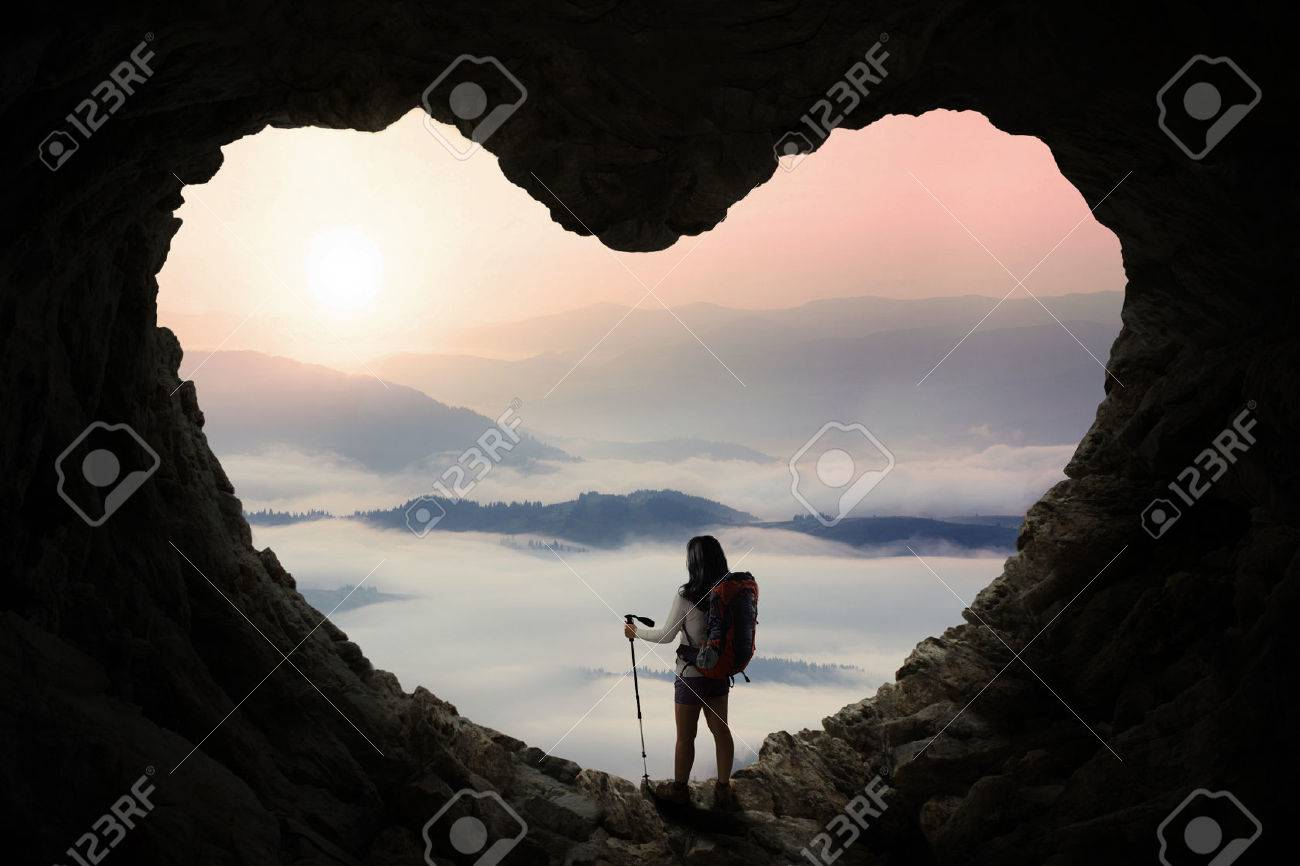 Silhouette of female hiker standing inside cave shaped heart symbol while holding stick pole and enjoy mountain view Banque d'images - 51941743