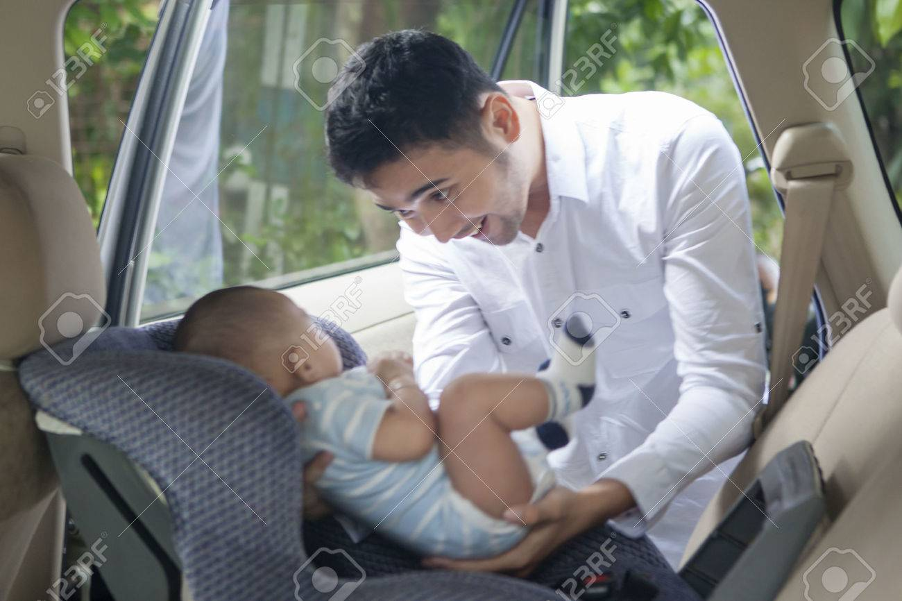 Portrait of young father putting his newborn baby on the car seat Banque d'images - 51941624