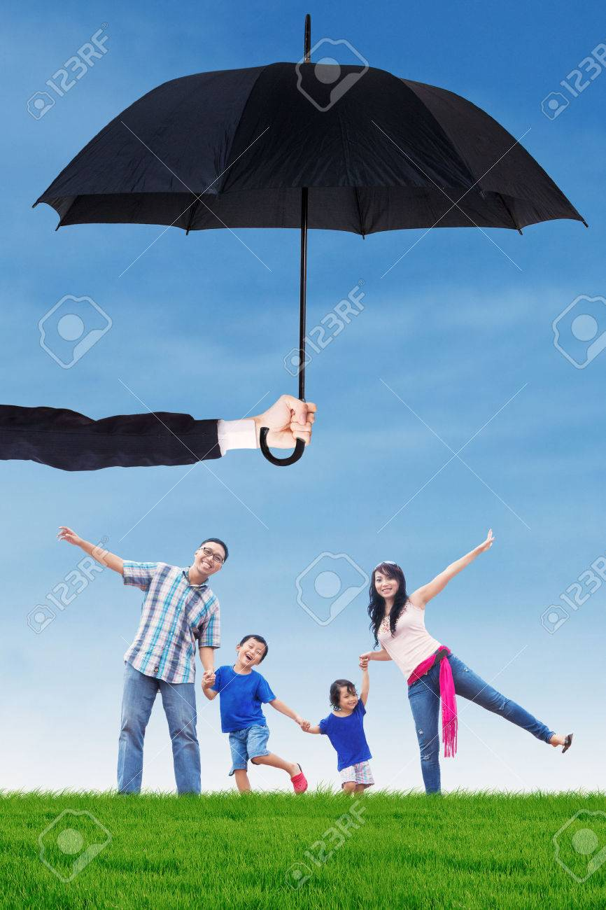 Image of happy family having fun on the meadow under umbrella. Life and family insurance concept - 58176414