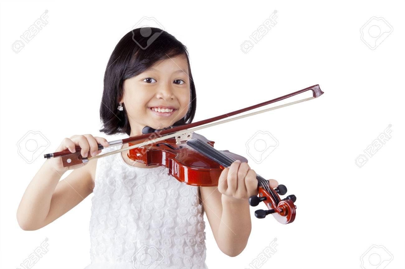 Portrait d'une petite fille joyeuse souriant à la caméra en jouant du violon dans le studio Banque d'images - 57977974