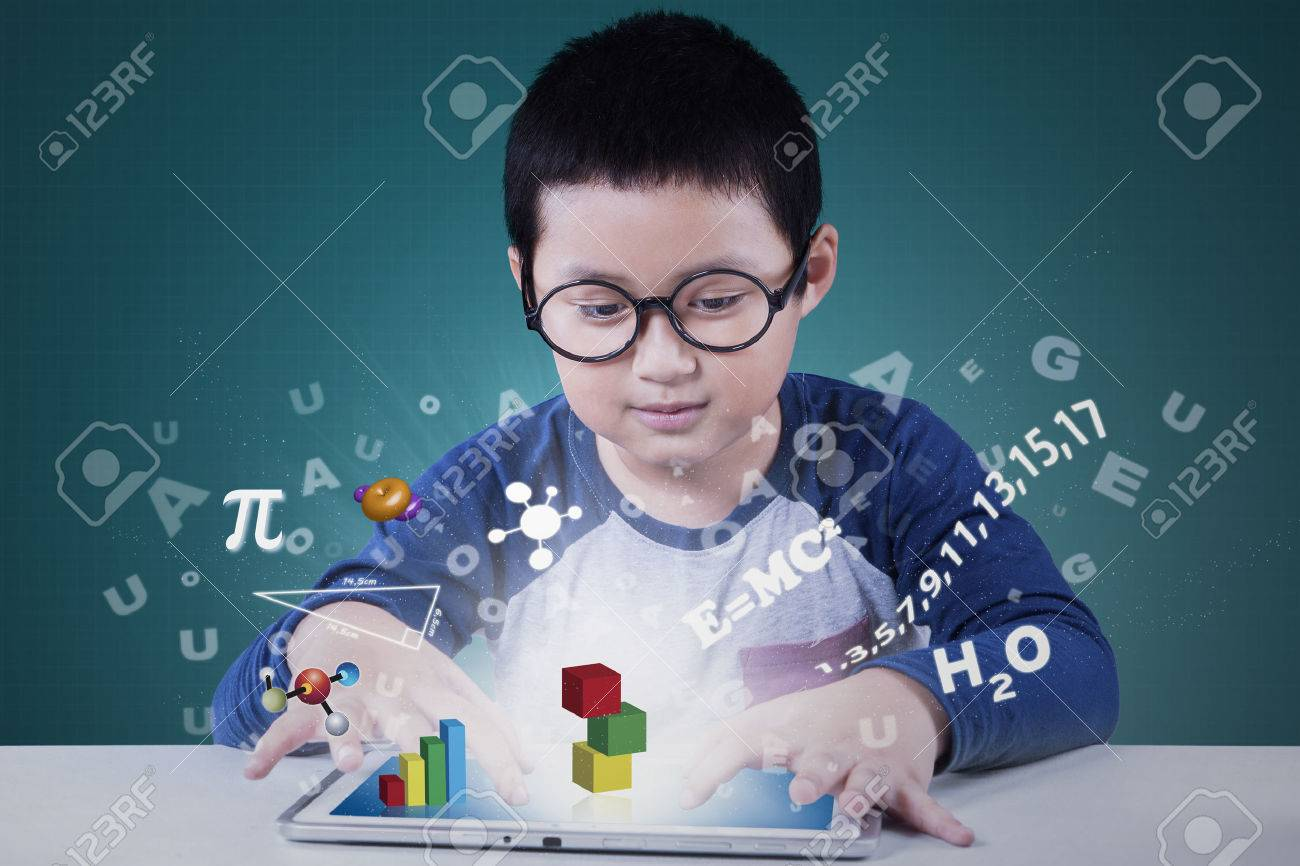 Portrait of a cute elementary school student using application on the tablet for studying Stock Photo - 57978685