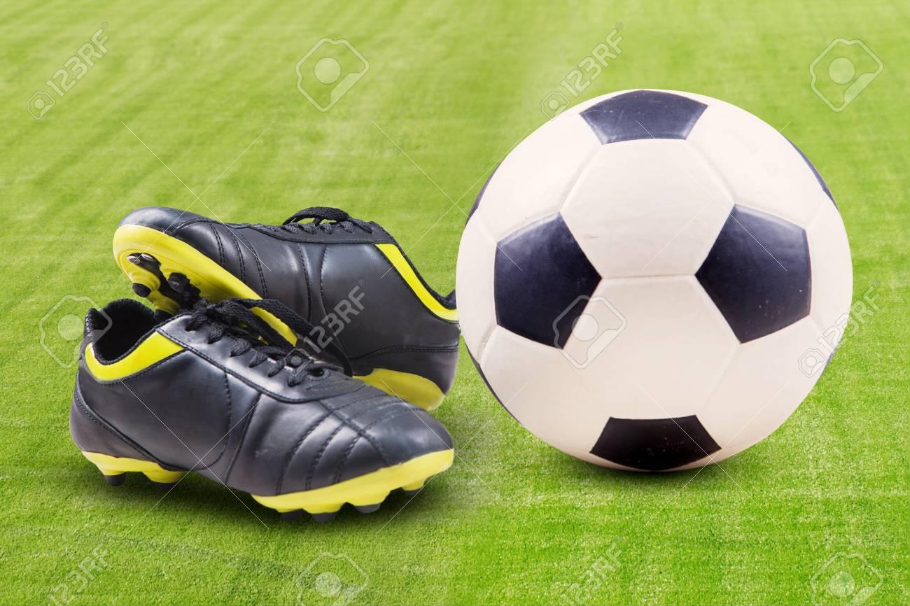 469220bb483e2 Cierre de la pelota de fútbol y zapatos en un césped verde Foto de archivo -